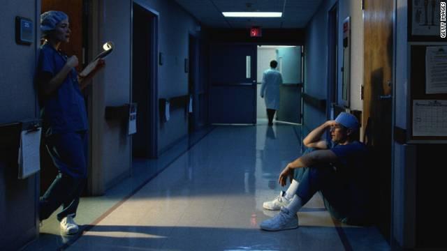 Doctor and nurse conferring in hospital corridor