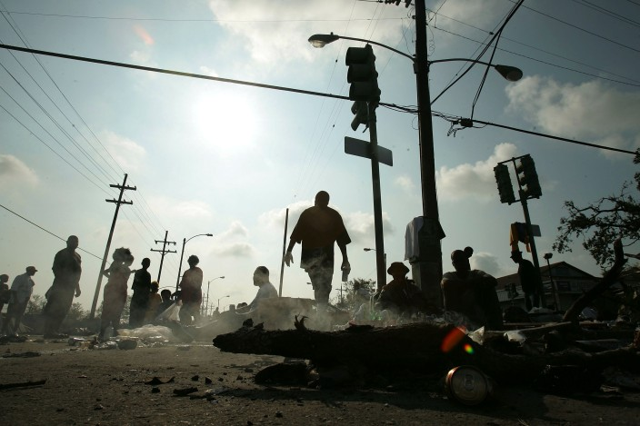 NEW ORLEANS - AUGUST 31: People wait for assistance after being rescued from their homes a day earlier in the Ninth Ward as a small fire burns after Hurricane Katrina August 31, 2005 in New Orleans, Louisiana. Devastation is widespread throughout the city with water approximately 12 feet high in some areas. Hundreds are feared dead and thousands were left homeless in Louisiana, Mississippi, Alabama and Florida by the storm. (Photo by Mario Tama/Getty Images)