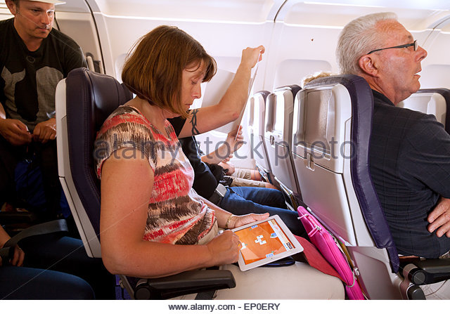 a-woman-passenger-on-a-plane-using-an-ipad-sitting-in-her-seat-in-ep0ery